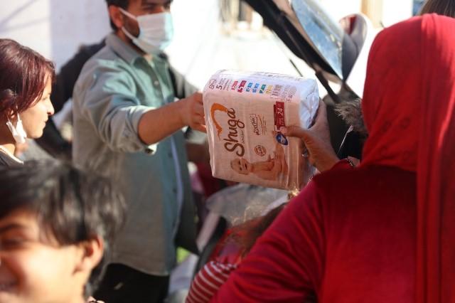 İhtiyaç sahibi ailelere bebek bezi ve yemek dağıttı